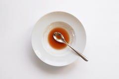 Placa con la cuchara y sobras de la sopa Fotografía de archivo libre de regalías