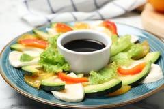 Placa con la ensalada fresca y el vinagre balsámico en cuenco en la tabla imagen de archivo libre de regalías