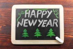 Placa con la Feliz Año Nuevo de la inscripción Imágenes de archivo libres de regalías