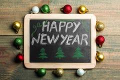 Placa con la Feliz Año Nuevo de la inscripción Foto de archivo