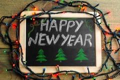 Placa con la Feliz Año Nuevo de la inscripción Foto de archivo libre de regalías
