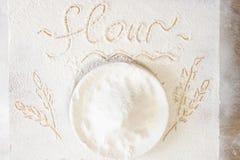 Placa con la harina en la tabla floured La imagen a mano de oídos del trigo y la palabra flour escrito en la tabla Estilo popular Foto de archivo
