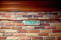 Placa con la salida de la inscripción en ruso en una pared de ladrillo sobre la puerta Fotos de archivo libres de regalías