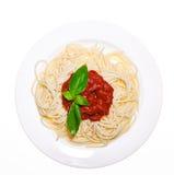 Placa con la salsa de espagueti y la albahaca Imagen de archivo libre de regalías