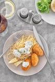 Placa con las croquetas y el spaghett de color salmón sabrosos Foto de archivo libre de regalías