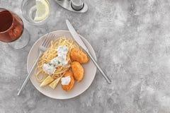 Placa con las croquetas y los espaguetis de color salmón sabrosos Fotos de archivo libres de regalías