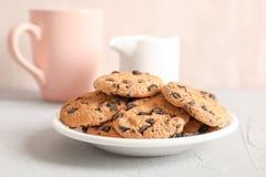Placa con las galletas de microprocesador de chocolate sabrosas y la taza borrosa de leche en fondo gris fotografía de archivo