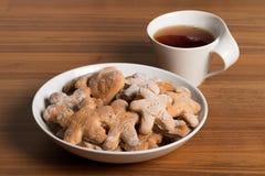 Placa con las galletas hechas a mano Taza de té en una tabla de madera imagenes de archivo
