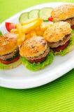 Placa con las hamburguesas sabrosas Foto de archivo libre de regalías