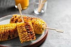 Placa con las mazorcas de maíz asadas a la parrilla deliciosas en la tabla gris imagen de archivo libre de regalías