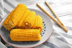 Placa con las mazorcas de maíz hervidas sabrosas y las pinzas de madera en la tabla, cierre encima de la visión imagenes de archivo