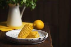 Placa con las mazorcas de maíz maduras en la tabla contra fondo oscuro fotos de archivo libres de regalías