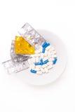 Placa con las píldoras médicas blancas y azules para tratar enfermedades Imagen de archivo