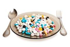 Placa con las píldoras y los cubiertos Foto de archivo