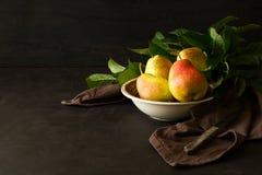 Placa con las peras y las manzanas maduras imágenes de archivo libres de regalías