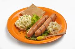 Placa con las salchichas alemanas, los purés de patata y la col amarga imagen de archivo libre de regalías