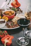 placa con las salsas, las patatas asadas, la carne asada a la parrilla con las verduras y los vidrios de vino en la tabla Imagen de archivo libre de regalías