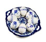Placa con los huevos de Pascua pintados en el fondo blanco Imagen de archivo