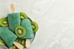 Placa con los polos deliciosos del spirulina y kiwi en el fondo gris, visión superior imagen de archivo