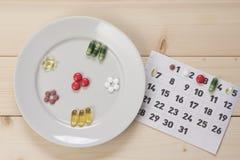 Placa con píldoras y un calendario Fotografía de archivo