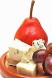 Placa con queso, la pera y las uvas Foto de archivo