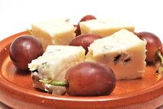 Placa con queso y uvas Fotografía de archivo