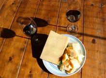 Placa con queso y vino tinto del regiano del parmigiana foto de archivo