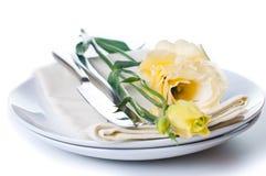 Placa, cuchillería y flor amarilla Imagenes de archivo