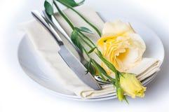 Placa, cuchillería y flor amarilla Fotos de archivo