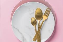 Placa, cuchillo del oro, bifurcaci?n y cuchara de m?rmol en fondo rosado platos y cubiertos, placa con las cucharas y bifurcaci?n fotos de archivo libres de regalías