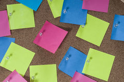 Placa da cortiça completamente com notas coloridas do cargo Foto de Stock