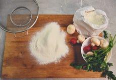 Placa da cozinha com os ingredientes para cozinhar a pizza fotografia de stock royalty free
