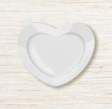 A placa da forma do coração wodden sobre a tabela Fotografia de Stock Royalty Free