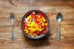 Placa da salada fresca com verdes, tomates, pimentas, azeitonas e queijo Forquilha da colher Fotos de Stock
