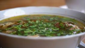 Placa da sopa tradicional Georgian de Khashlama em uma tabela de madeira em um restaurante vídeos de arquivo