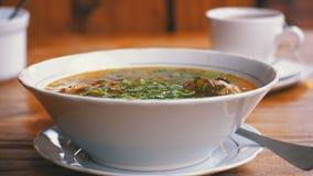 Placa da sopa tradicional Georgian de Khashlama em uma tabela de madeira em um restaurante video estoque