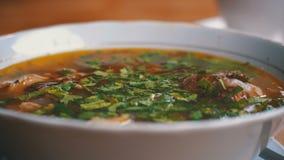 Placa da sopa tradicional Georgian de Khashlama em uma tabela de madeira em um restaurante filme