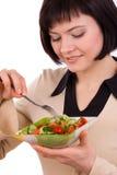 Placa da terra arrendada da mulher com salada e comer. foto de stock royalty free