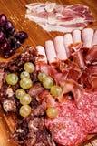 Placa das carnes frias na placa de corte de madeira Fotos de Stock