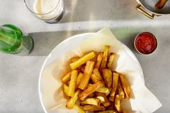 Placa das fritadas com ketchup e vidro da cerveja escura Imagem de Stock