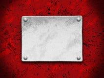 Placa de acero en un fondo rojo del grunge Foto de archivo
