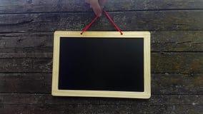 Placa de anúncio em branco Esvazie a placa preta contra a parede de madeira do fundo video estoque