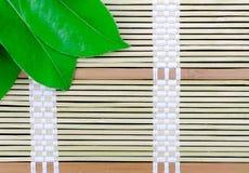 Placa de bambú con las hojas Imagenes de archivo