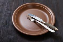 Placa de Brown com faca paralela, colher na obscuridade Imagens de Stock
