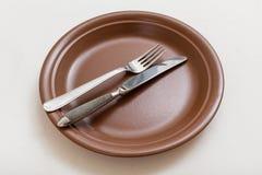 Placa de Brown com faca paralela, colher no branco Fotos de Stock