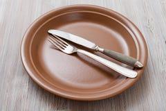 Placa de Brown com faca paralela, colher no cinza Imagens de Stock