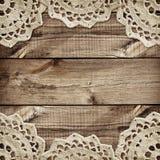 A placa de Brown e pequenos de madeira fazem crochê doilies nas beiras Fotografia de Stock Royalty Free