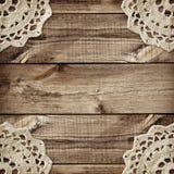 A placa de Brown e pequenos de madeira fazem crochê doilies nos cantos Imagens de Stock