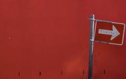 Placa de calle blanca de la flecha en un fondo rojo Foto de archivo libre de regalías