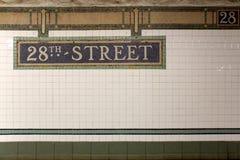 Placa de calle del subterráneo de la estación de New York City 28va cuarta en la pared de la teja Foto de archivo libre de regalías